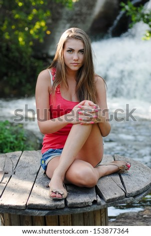Young woman looking at camera near waterfall in summer outdoors