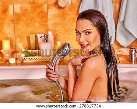 Young woman looking at camera take bubble  bath. - stock photo