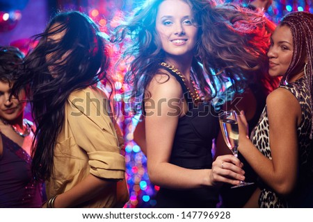 Young woman looking at camera while dancing at nightclub among her friends - stock photo