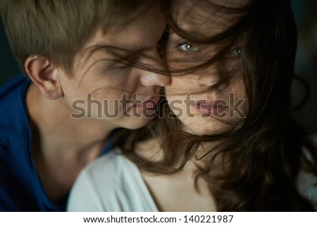 Young woman looking at camera with her sweetheart near by