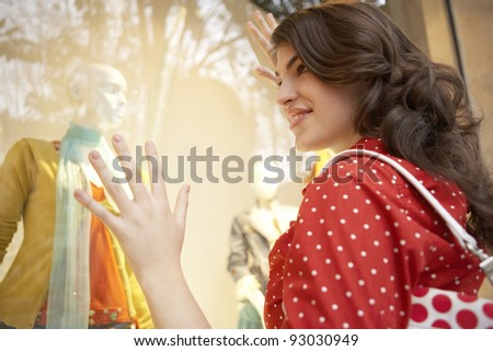 Young woman looking at fashion shop window, day dreaming. - stock photo