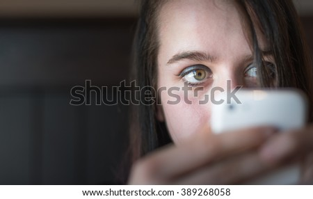 Young woman looking at her cellular phone while using it.  Girl makes contacts in digital world of social networks, connecting people together.  Hands holding phone, partially block lower face.