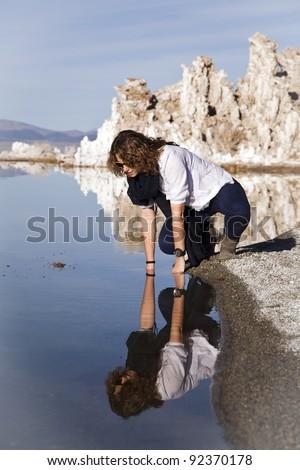 Young woman looking at her reflection at Mono Lake, California! - stock photo