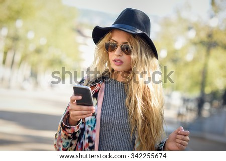 Young woman looking at her smartphone in urban background. Girl wearing jacket, hat, sweater and sunglasses.