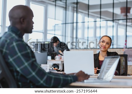 Young woman looking at male colleague while sitting at a table with laptop. African executive discussing work with coworker. - stock photo
