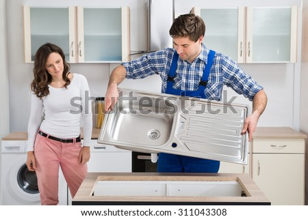 Young Woman Looking At Male Worker Carrying Steel Kitchen Sink In Kitchen