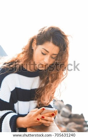 Young woman looking at mobile phone in seaport