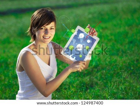 Young  woman looking at modern tablet with abstract light and various diagrams