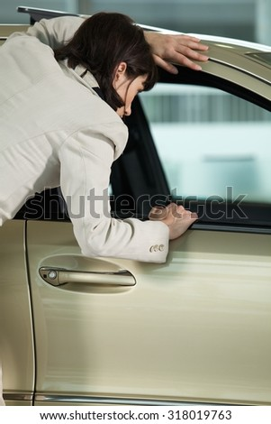 Young woman looking at new car