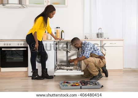 Young Woman Looking At Repairman Repairing Dishwasher In Kitchen - stock photo