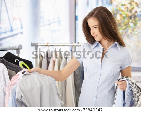 Young woman looking at shirt in clothes store, smiling.?