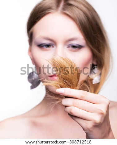 Young woman looking at splitting hair ends
