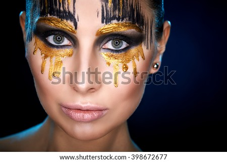 Young woman looking at the camera with fantasy make up face art studio shot. Copy space. High resolution