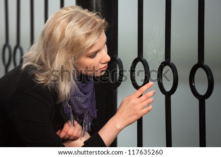 Young woman looking at the spider web - stock photo
