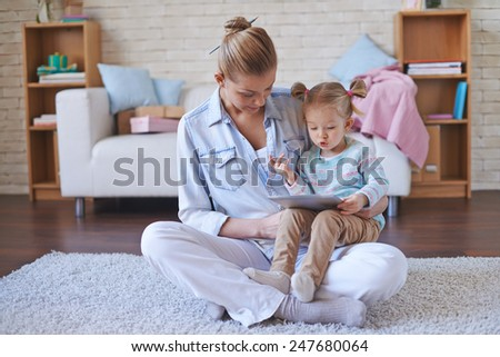 Young woman looking at touchscreen held by daughter at leisure  - stock photo