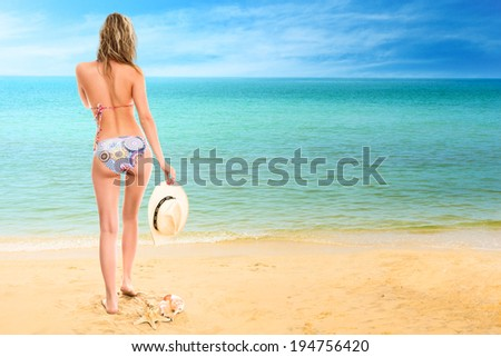 Young woman looking at tropical sea. Rear view outdoor - stock photo