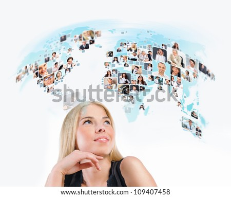 Young woman looking at virtual worldmap with photo of different people worldwide. International communication or online community concept. - stock photo