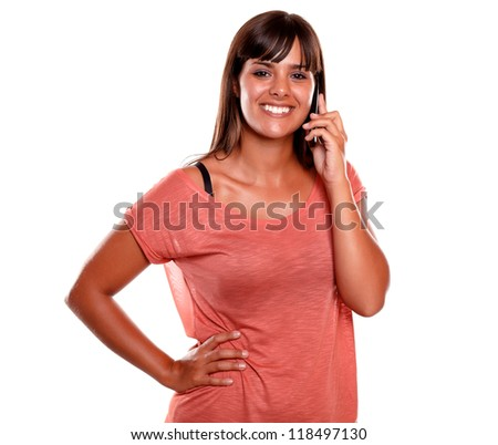 Young woman looking at you while is talking on mobile phone against white background