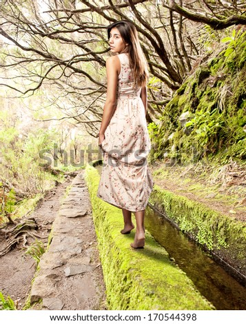 young woman looking back walking on a forest - stock photo