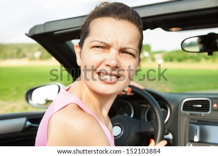 Young Woman Looking Back While Travelling In Car - stock photo