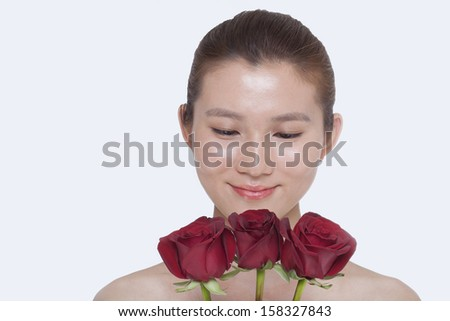 Young woman looking down at a bunch of red roses