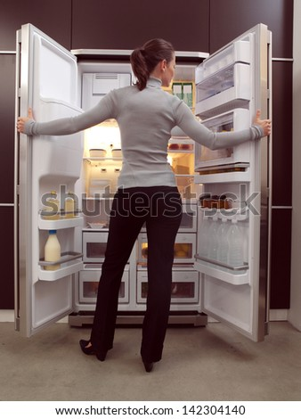 Young woman looking for something to eat - stock photo