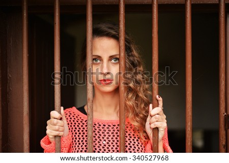 Young woman looking from behind bars. trapped woman behind iron bars