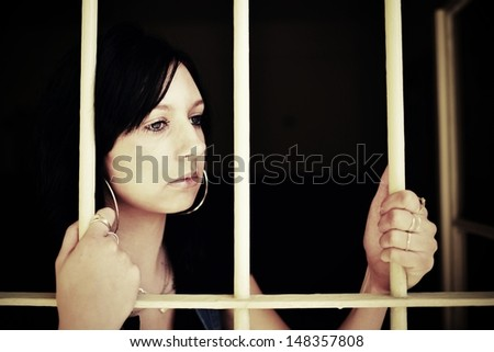 Young woman looking from behind the bars - stock photo