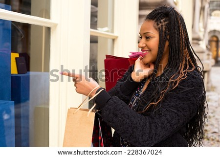 young woman looking in a shop window pointing. - stock photo