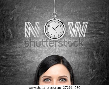 young woman looking in front of her and tthinking about present opportunities and time. A pocket watch and the word 'now' over her head. Black background. Front view. Concept of present moment. - stock photo