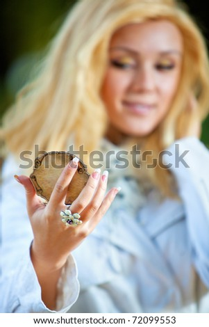 Young woman looking on mirror. Focus on hand. - stock photo