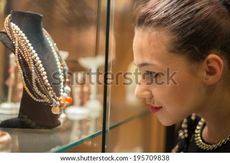 Young woman looking on the jewelry shop window - stock photo
