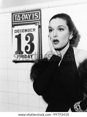 Young woman looking shocked after seeing Friday the 13th on a calendar - stock photo