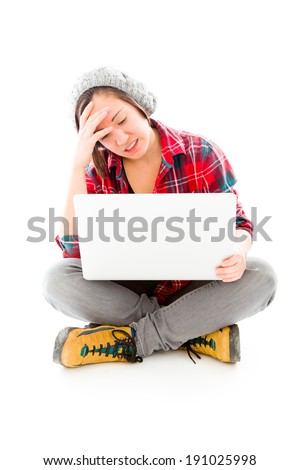 Young woman looking stressed using laptop - stock photo