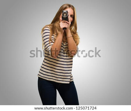 Young Woman Looking Through A Camera against a grey background - stock photo