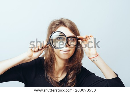 young woman looking through a magnifying glass - stock photo