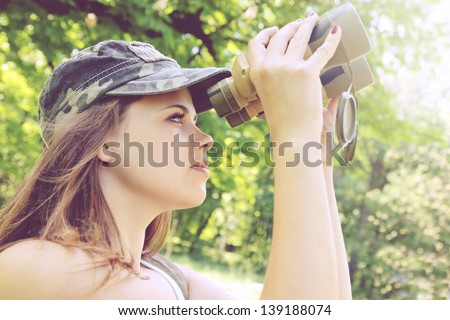 Young woman looking through binoculars on the nature - stock photo