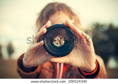 Young woman looking through camera lens - stock photo