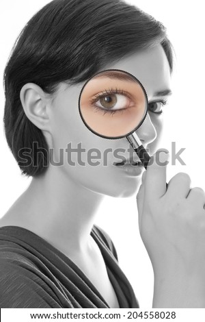 young woman looking through magnifying glass - stock photo