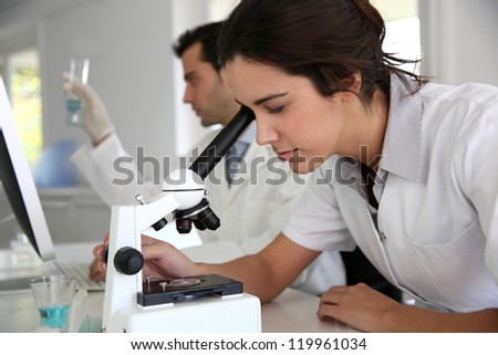Young woman looking through microscope lense - stock photo