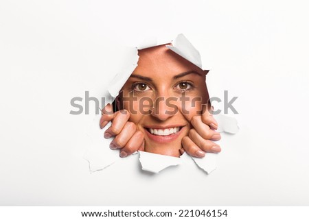 Young woman looking through paper rip on white background