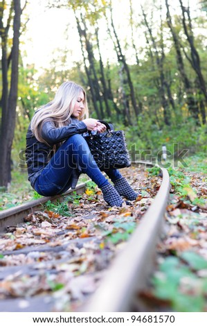 Young woman looking to handbag on a railroad - stock photo