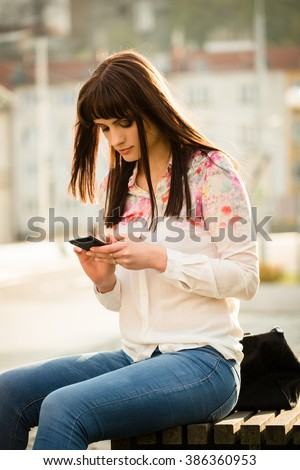 Young woman looking to her smartphone - sitting on bench in street