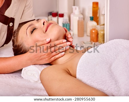 Young woman looking up getting facial  massage in beauty spa. - stock photo