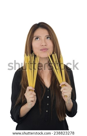 Young woman looking up while holding raw spaghetti against a white background - stock photo