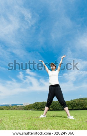 young woman looking up with open arms over sky
