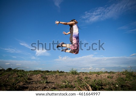 young woman looking up with open arms over sky background.