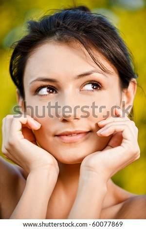 Young woman looks askance, against autumn foliage. - stock photo