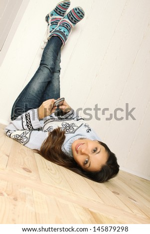 Young woman lying at home with a mobile phone