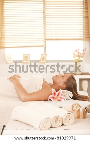 Young woman lying at massage parlour, towels and massage equipment in front.? - stock photo